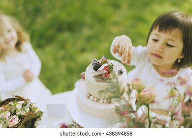 two sweet little flower children playing outside in the wedding decoration and snack straight from the beautifully decorated wedding cake