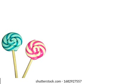 Two sweet lollipops with red, blue, turquoise and white spiral color stripes on a wooden stick isolated on a white background. Holiday card birthday concept.