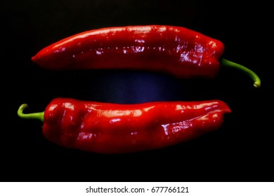 Two sweet red pointed peppers on black background