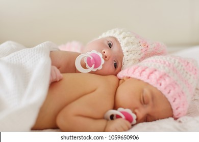 two sweet twins are laying on the bed