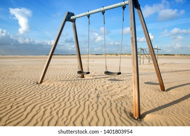 two swings in the sand by the beach and blue sky