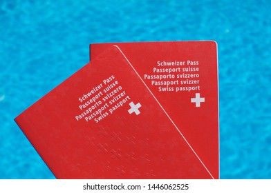 Two Swiss passport held in front of blue pool water background