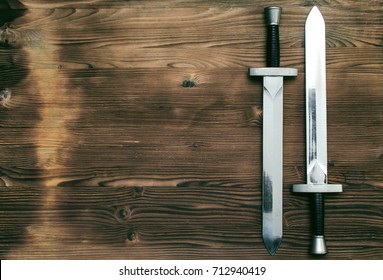 Two swords on burnt wooden surface with copy space background.