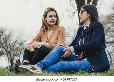 Two sylish girls sitting on the grass and talking sad life stories, in park on beautiful spring day