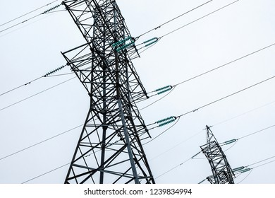 Two symmetrical metal electrical towers with wires. Overcast weather