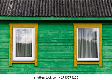 two symmetrical windows on a wall of an old wooden house in Latgale, Latvia