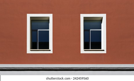 Two symmetry windows in a red facade of a building. Horizontal composition.