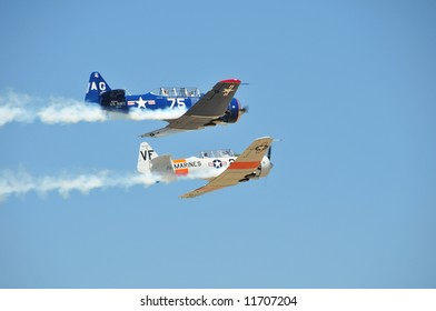 Two T-6 type military aircraft fly by with smoke trails