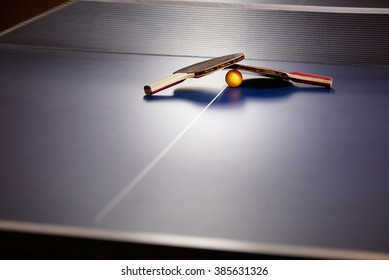 Two table tennis or ping pong rackets and ball on a blue table with net