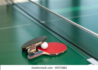 Two table tennis or ping pong rackets and balls on a green table with net; shallow DOF, focus on rackets