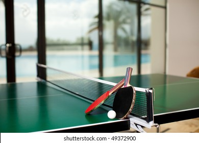 Two table tennis or ping pong rackets and balls on a green table with net, swimming pool, palm tree and sea in the background; shallow DOF, focus on rackets