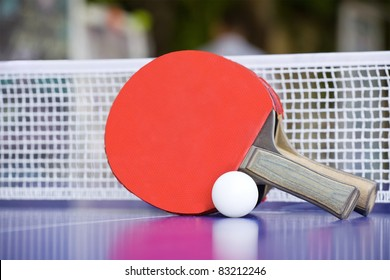 Two table tennis or ping pong rackets and balls on a blue table with net; shallow DOF, focus on rackets