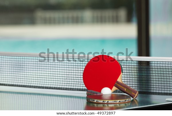 Two table tennis or ping pong rackets and ball on a green table with net, swimming pool in the background; shallow DOF, focus on rackets