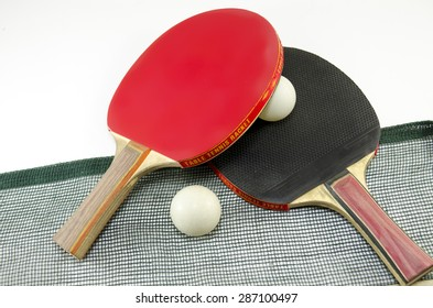 Two table tennis rackets one on top of the other and an old net isolated on white. One paddle is red and the other is black
