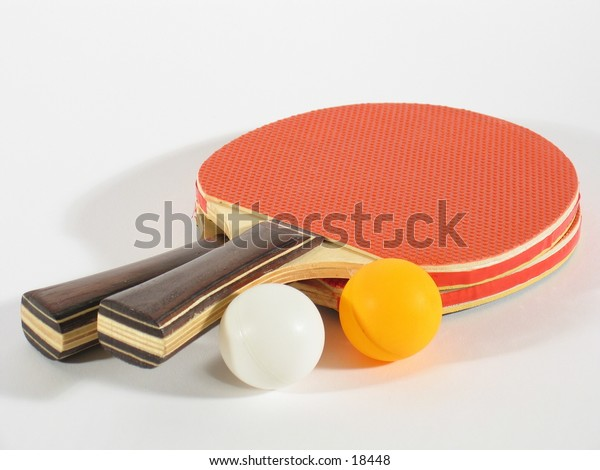 Two table tennis racks with a white and an orange ping pong ball.