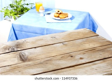 two tables-an empty antique wooden surface and another one with breakfast served, brioche filled with chocolate,a boiled egg and fresh juice