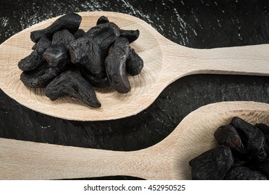 Two tablespoons with black garlic,cooking ingredients