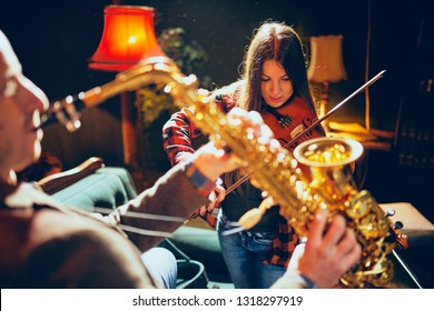 Two talented musicians playing violin and saxophone. Home studio interior.