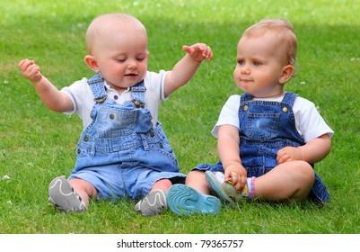 Two talking children on green meadow.