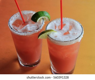 Two tall chilled glasses with fruity tropical drink, garnished with slices of lime, salt along the rim.