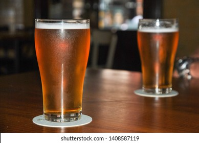 Two tall glasses of beer on a wooden table top