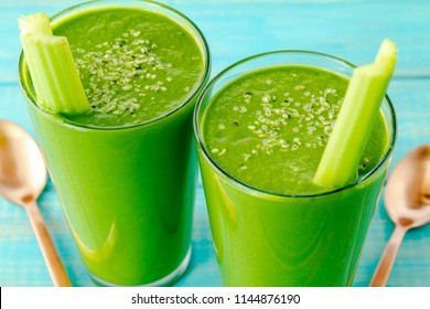 Two tall glasses filled with kale and spinach green smoothies garnished with celery stalks and hemp seeds with two copper spoons on side