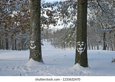 Two tall oak trees with faces made of snow stand before a scenic, snow covered hill covered in trees in winter