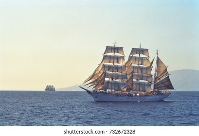 two tall ships leaving port in early evening under full sail