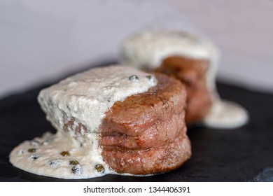 Two tall slices of tenderloin with green pepper sauce.