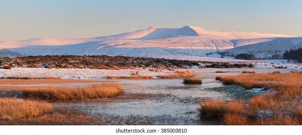 The two tallest peaks in south Wales - Pen Y Fan and Corn Du covered in snow and bathed in warm light.