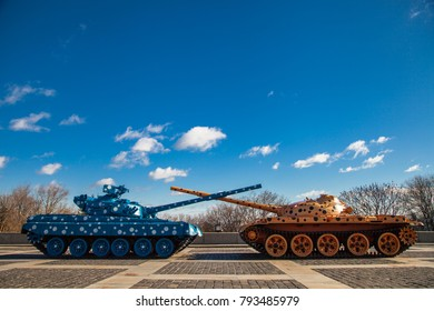 Two tanks with crossed guns, against the blue sky. Two tanks blue and orange in black and white point