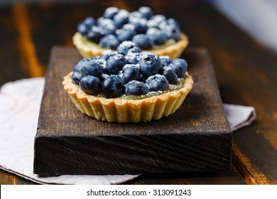 Two tartlets with lemon custard and blueberries on the wooden surface