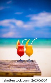 Two tasty alcoholic cocktails on background of turquoise sea