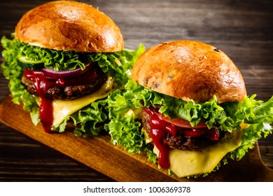 Two tasty burgers with cheese and ketchup served on cutting board