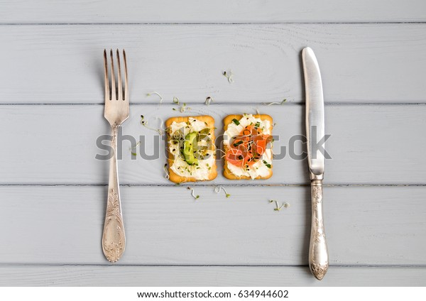 Two tasty crackers with cream cheese, salmon, cucumber and greens. Appetizers on grey table with fork and knife. Healthy snacks, diet concept. Top view, flat lay