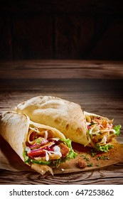 Two tasty doner kebabs filled with mixed vegetables and shaved spit roasted meat in tortilla wraps with rustic copy space above