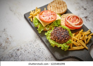 Two tasty grilled home made burgers with beef, tomato, onion and lettuce. French frides on side. Top view with copy space