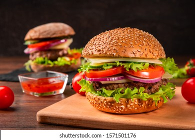 Two tasty humburgers with tomatoes and sauce