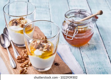 Two tasty natural desserts with Greek yogurt, raw fresh walnuts and a topping of honey served in individual glasses
