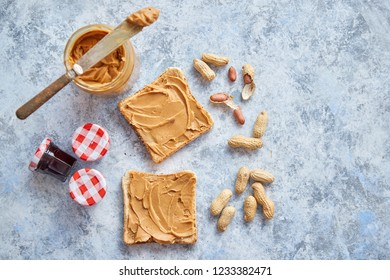 Two tasty peanut butter toasts placed on stone table. With small jars of fruit jam big peanut butter container. Knife on side. Above view with copy space
