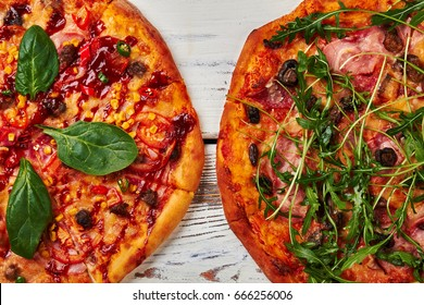 Two tasty pizzas, wooden background. Italian pizzas with meat and herbs. Delicious cuisine.