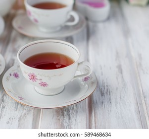 two teacups, teapot and milk jug, festive tableware tea service with floral pattern. holiday concept.