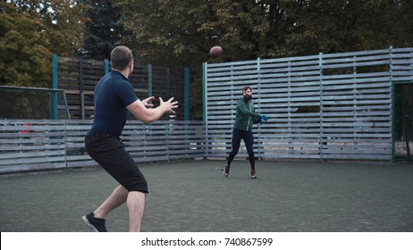 Two teammates practising ball passing on field while playing American football
