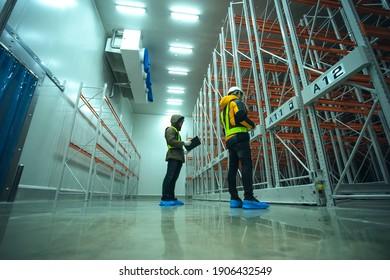 Two technician inspector check machine shelf in cold warehouse. Team professional installation shelf machine in cold storage room. - Shutterstock ID 1906432549