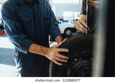 Two technicians checking the depth of tire tread with measuring instrument. Mechanics inspecting the tire in workshop. Closeup shot with focus on hands of mechanics.