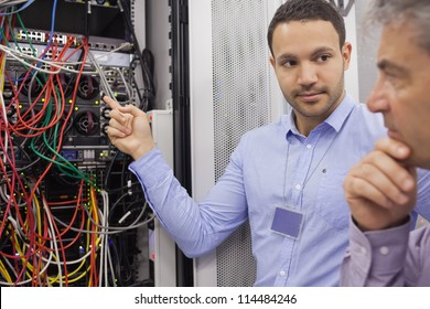 Two technicians looking at wiring of servers in data center