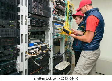 Two technicians measure the signal level in the fiber optic cable. Serving a central router in a server room. Two people work in a modern data center.