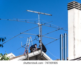 two technicians working on a condominium roof to fix a TV antenna