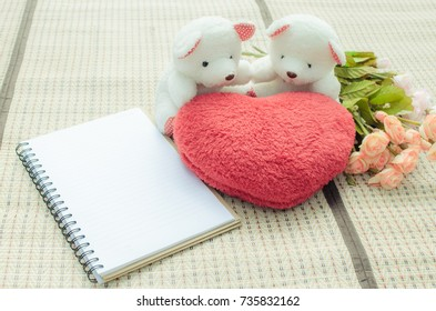 two teddy Bear with love and notebook in park