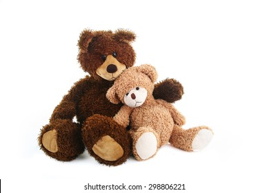 Two teddy bears, bigger and smaller, are sitting close to each other like they are best friends.